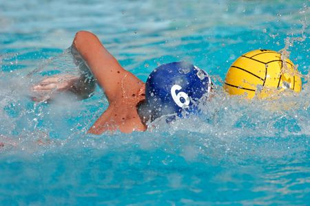 Water polo player swimming for the ball