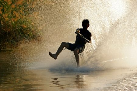water skier: Silhouette of a barefoot skier with backlit water spray Stock Photo