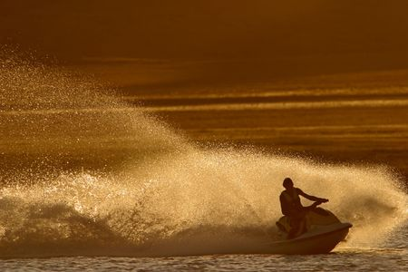 Backlit jet ski with water spray, late afternoon  Stock Photo