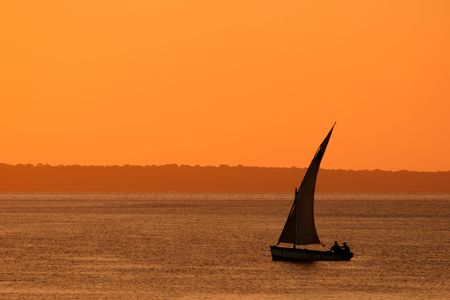 Traditional sail boat called a dhow at sunset, Vilanculos coastal sanctuary, Mozambique  photo
