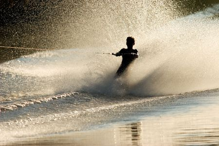 water skier: Silhouette of a barefoot skier with backlit water spray