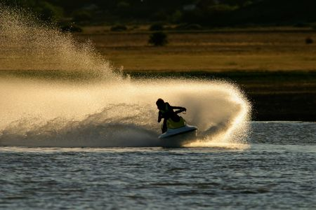 Backlit jet ski with water spray, late afternoon