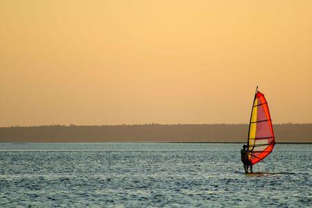 exhilarating: Backlit windsurfer at sunset on calm coastal water