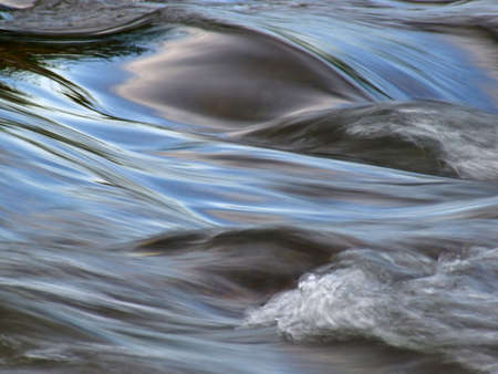 rapid: Flowing water with the reflection of the blue sky taken with a slow shutter speed   Stock Photo
