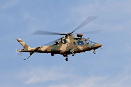 camouflaged: A camouflaged military helicopter in flight  Stock Photo