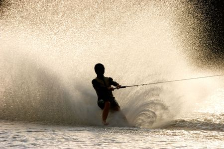 water  skier: Silhouette of a barefoot water skier with backlit water spray