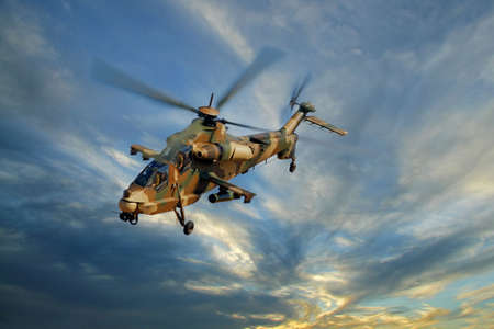 A camouflaged military helicopter in flight against a dramatic sky