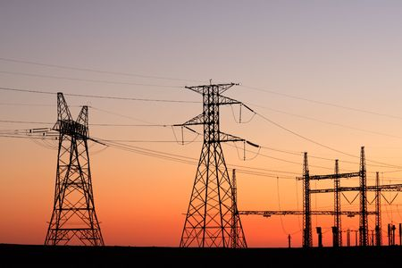 powerline: Silhouetted power pylons against a red sky at sunset Stock Photo