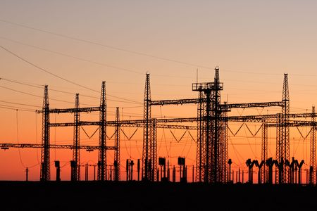 conductor electricity: Silhouetted power pylons against a red sky at sunset Stock Photo