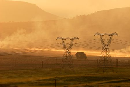 Backlit power pylons in mist at sunset photo