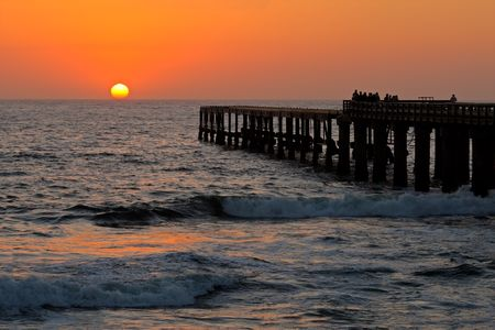 View of a silhouetted coastal pier with people watching a glowing sunset Stock Photo - 5498409