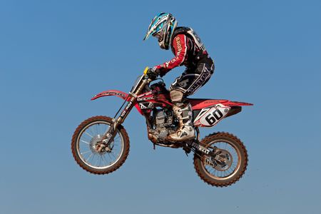 Bloemfontein, South Africa - July 19, 2009 - Motocross rider jumping through the air during a national motocross racing event