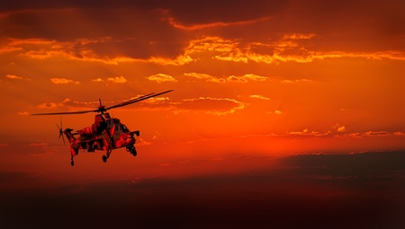 military aircraft: A camouflaged military helicopter in flight against a dramatic red sky