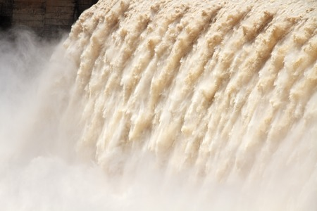 sluice: Strong flowing water with water spray from the open sluice gates of a large dam