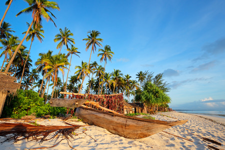 Wooden sailboat  - dhow - and palm trees on a tropical beach of Zanzibar island photo