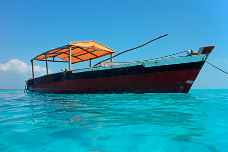 Wooden boat floating on the clear turquoise water of Zanzibar island photo
