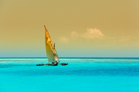 Wooden sailboat  - dhow - on the clear turquoise water of Zanzibar island photo