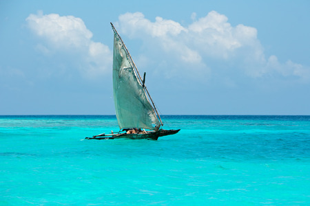 Wooden sailboat on the clear turquoise water of Zanzibar island photo