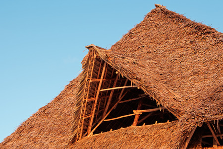 thatched: Rustic African thatched roof against a blue sky with clouds