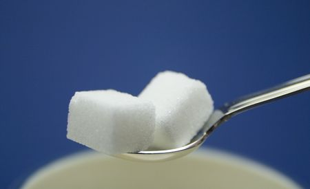 Two sugar cubes in a silver spoon above a cup.  Isolated on blue background