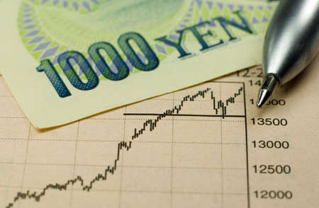 yen: 1000 Yen banknote with pen and rising stock chart. Stock Photo
