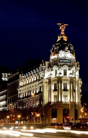 Beginning of Gran Via in Madrid at night.  The Metropolis building from 1905 stands at the start of the Gran Via and is known for its architecture. photo