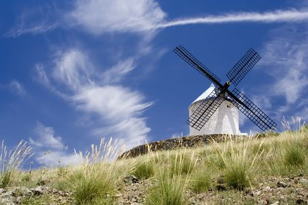 Medieval windmill dating from the 16th century on a hill overlooking the town of Consuegra in Toledo province, Castilla La Mancha, central Spain.  Made famous in Miguel de Cervantes Saavedras novel Don Quijote de la Mancha, these windmills are situated a photo