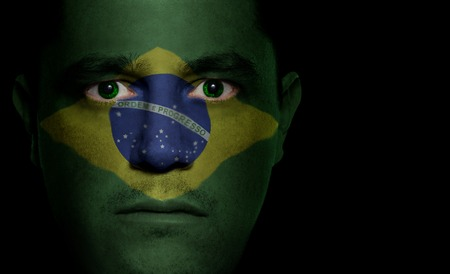 Brazilian flag paintedprojected onto a mans face.
