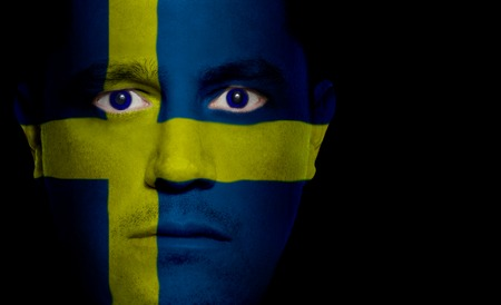 sweden flag: Swedish flag paintedprojected onto a mans face. Stock Photo