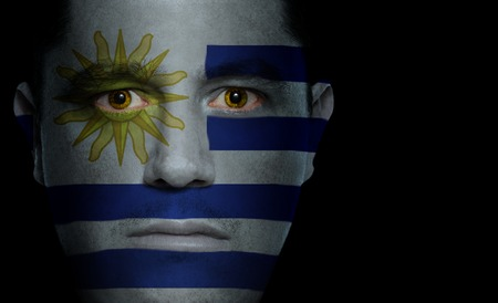 Uruguayan flag paintedprojected onto a mans face. photo