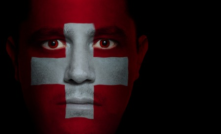 Swiss flag paintedprojected onto a mans face.