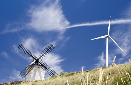 Medieval Spanish windmill dating from the 16th century and modern 20th century wind turbine on a hill in summer. Stock Photo - 1659545