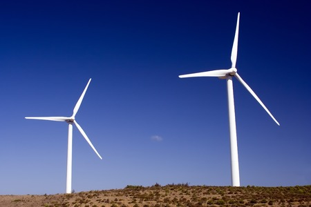 Two wind turbines standing in the savannah in western Algarve, Portugal. photo