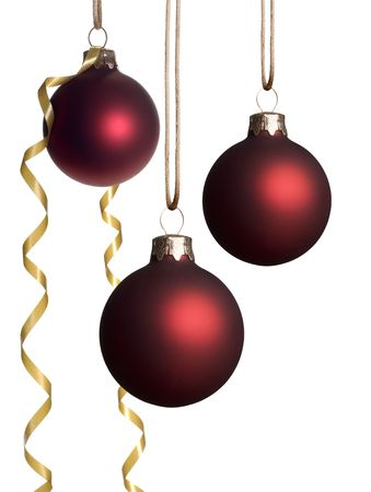 Red Christmas ornaments hanging with a gold ribbon isolated on a white background. Stock Photo