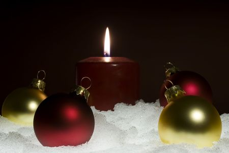 Red candle sitting in a base of snow with red and gold glass ornaments in the foreground. photo