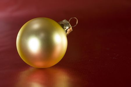 matte: Gold Christmas ornament on red wrapping paper
