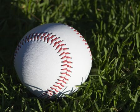 Close up of a new baseball sitting in grass photo