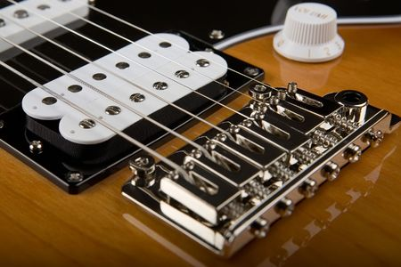 Closeup of body of electric guitar with view of bridge and pickups photo