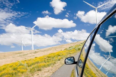 Green energy concept with wind turbines reflected in a car window photo