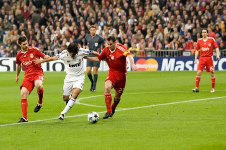 MADRID - FEB. 25, 2009: Real Madrid player Raul Gonzalez fights off Liverpool players Jamie Carragher and Xabi Alonso during their Champions League second round match.