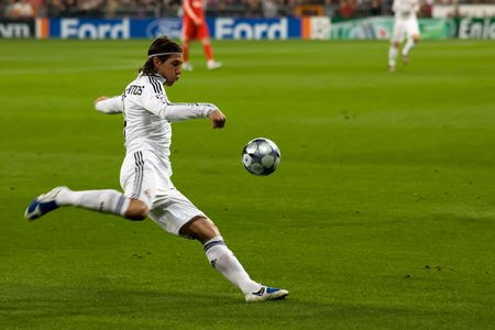 sergio: MADRID - FEB. 25, 2009: Real Madrid player Sergio Ramos crosses a ball during their Champions League second round match against Liverpool FC.