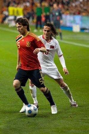 silva: MADRID - MAR. 28, 2009: Spains David Silva holds the ball against a challenge from Turkish player Tuncay Sanli during the second half of Spains 1-0 victory over Turkey in their World Cup Qualifier.