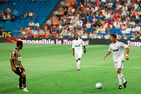 MADRID - JUL. 26, 2009: Cristiano Ronaldo looks to dribble around a defender in his first match in the Santiago Bernabeu stadium during Real Madrids 1-1 draw with Al Ittihad in the Peace Cup.