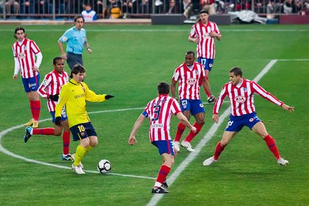 FEB. 14, 2010 - Barcelona player Lionel Messi tries to dribble through the defense during Atletico Madrids 2-1 victory over FC Barcelona in Madrid, Spain.