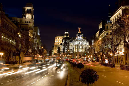 Calle de Alcala in Madrid at night.  The Metropolis building from 1905 stands at the start of the Gran Via and is known for its architecture.