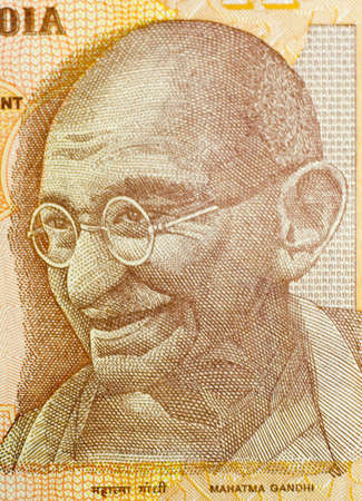 rupees: Close-up of ten Indian rupees banknote.  Features Mahatma Gandhi.