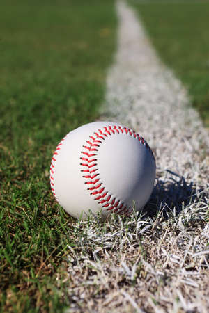 foul: Close-up of a baseball on the outfield foul line.