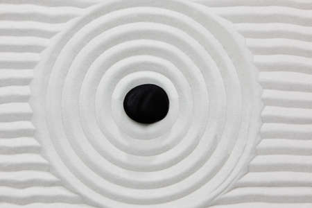 Close-up of a black stone on white raked sand in a Japanese ornamental or zen garden. Stock Photo
