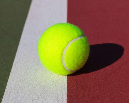 end line: Primer plano de una pelota de tenis en la l�nea final en una cancha de tenis. Foto de archivo