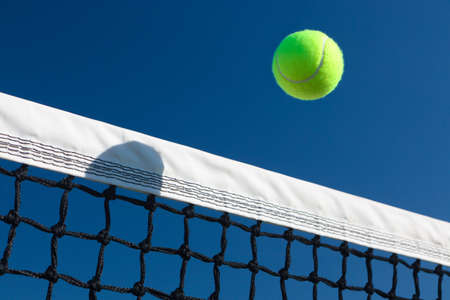 in net: Close-up of a tennis ball going over the net with a blue sky background.